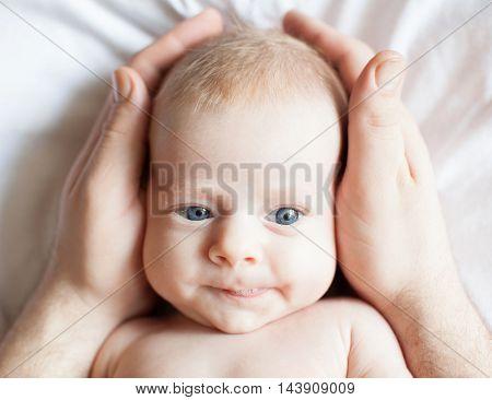 Baby in father's hands. Happy newborn