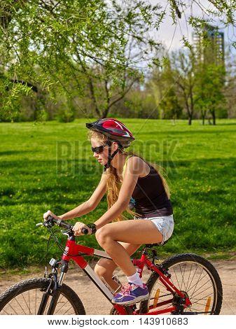Girl rides bicycle. Girl in cycling riding on bicycle lane . Incorrect landing on bike.