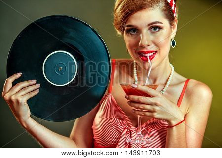 Girl in pin-up style keeps vinyl record and drink martini cocktail . Pin-up retro female style. Girl pin-up style wearing red dress