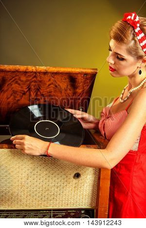 Girl in style keeps vinyl record. Pin-up retro female style. Girl pin-up style wearing red dress