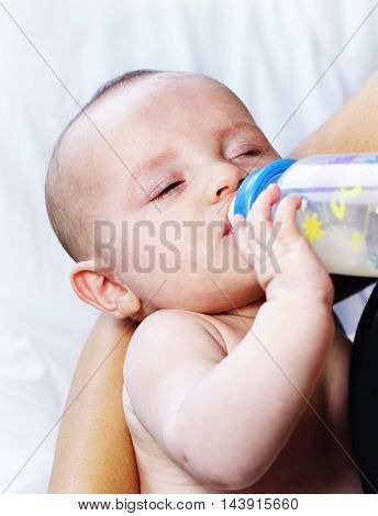 Beautiful baby drinking milk. baby with shut eyes and baby bottle, close-up shot.