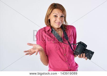 Middle aged woman holding dslr camera shrugging shoulders, beginner hobby
