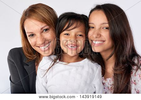 mixed race woman family mom and daughters happy together posing for portrait in studio isolated background