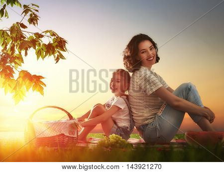 Family picnicking together. Young mother and her child daughter girl enjoying a healthy outdoor meal sitting together on green grass in summer park.
