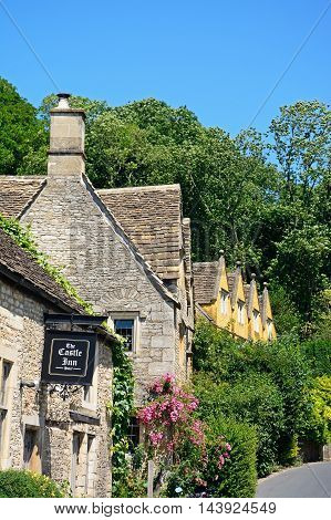 CASTLE COMBE, UNITED KINGDOM - JULY 20, 2016 - Cotswold stone buildings and part of The Castle Inn in the village centre Castle Combe Wiltshire England UK Western Europe, July 20, 2016.
