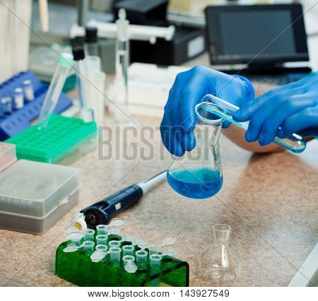scientist with test tubes and flasks conducting an experiment in a science lab