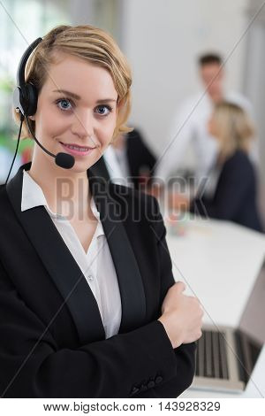 Portrait of a smiling creative businesswoman with earpiece in office