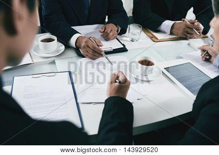 Hands of business people or lawyers analyzing documents on table