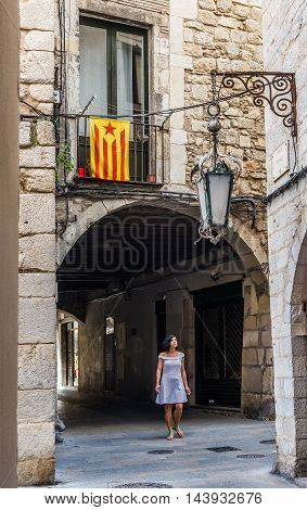 Girona Spain - July 30 2016. Latin American women walking under a flag of independence movement of Catalonia called Estelada (unofficial) in a street of the downtown of Girona Costa Brava Catalonia Spain.