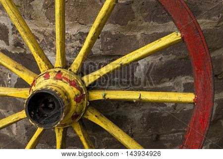 detail of old wagon wheel with metal rim leaning on a stone wall