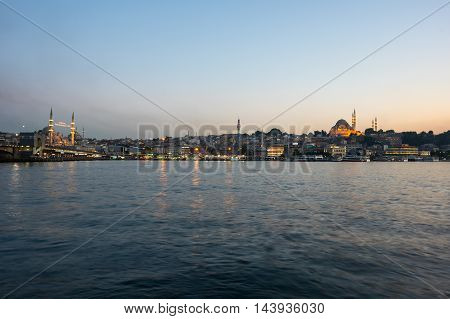 ISTANBUL TURKEY - JUNE 20 2015: Night view on the Suleymaniye Mosque New Mosque and fishing boats in Eminonu Istanbul Turkey