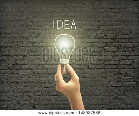 Male hand holding abstract illuminated lightbulb with text on dark brick wall background. Idea concept