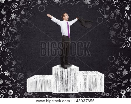 Attractive businessman celebrating victory on abstract podium sketch with business icon drawings around. Concrete wall background. Winner concept
