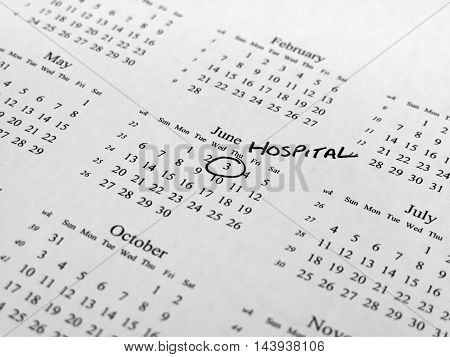 Generic calendar with hospital appointment circled with shallow depth of field centred on highlighted date