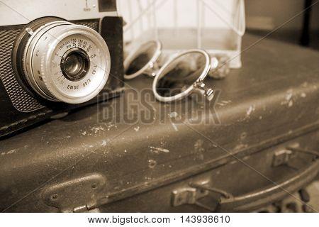 Retro camera, sunglasses and suitcase in sepia, travel conception