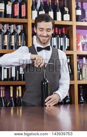 Bartender Using Corkscrew To Open Wine Bottle