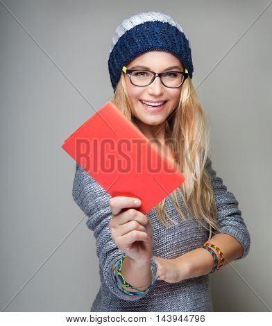 Portrait of a nice student girl with school book in hand over gray background, wearing stylish hat and glasses, education in the university