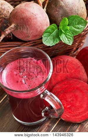 Beetroot juice on wooden background with beetroots and mint leaves in woven basket