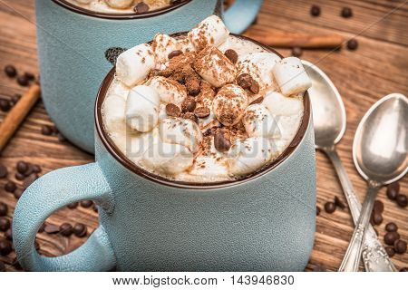 Cocoa with marshmallows and chocolate on a wooden table.