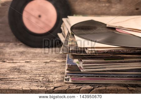 stack of old records on the old wooden background in vintage style (sepia)