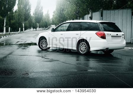 Saratov, Russia - August 28, 2014: Car Subaru Legacy stay on asphalt road and reflected in puddle in the city at daytime