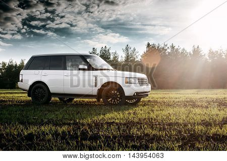 Saratov, Russia - September 01, 2014: Car Land Rover Range Rover stand on green field near forest at sunset