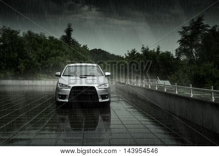 Moscow, Russia - June 18, 2016: Gray car Mitsubishi Lancer stay and reflect in wet road in heavy rain at daytime on Moscow city