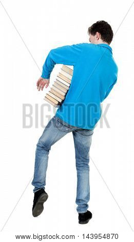 A man carries a heavy pile of books. back view. Rear view people collection.  backside view of person.  Isolated over white background. The curly-haired student in a blue warm jacket came out of the