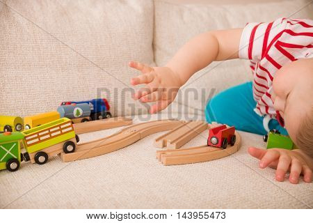 Close-up portrait of adorable toddler boy playing with railroad and colorful trains. Indoors. Early learning and development. Education.