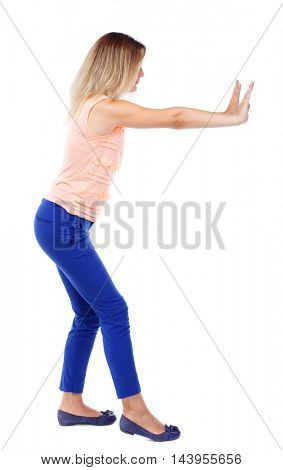 back view of woman pushes wall.  Isolated over white background. Rear view people collection. backside view of person. Blonde in blue pants shoves it to the side.