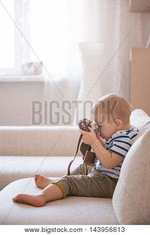 Cute adorable toddler boy sitting on the sofa in the living room and playing with vintage photo camera. Child taking picture with old camera. Future photographer. Kid with retro camera.