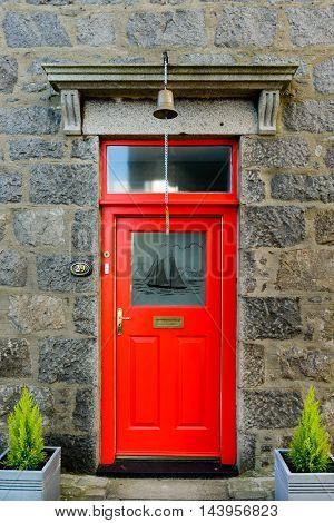 FOOTDEE (Fittie) ABERDEEN SCOTLAND UK - JUNE 21 2016: Red door entrance to a cottage in the small village of Footdee (aka Fittie). A nineteenth century fishing village close to entrance of Aberdeen harbour.
