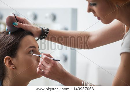 Make-up artist applying colors to model