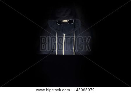 Cyber criminal in a hooded type with an unknown face sits at a laptop computer in the dark committing cyber crimes and hacking activities.