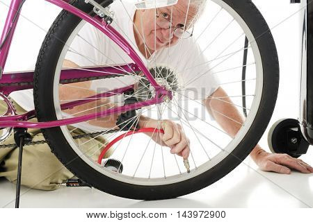 A senior man looking the the viewer through the spokes of the girl's bike tire that he's filling with the hose for an air compressor.  On a white background.