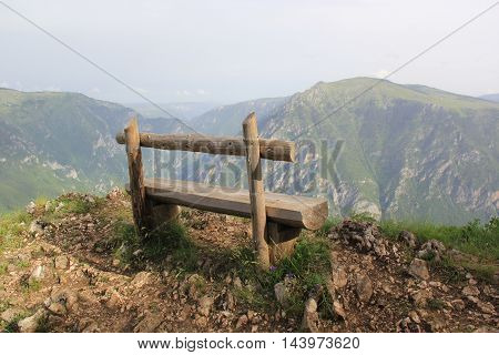 Lonely wooden bench on the edge of a high precipice overlooking the deep abyss