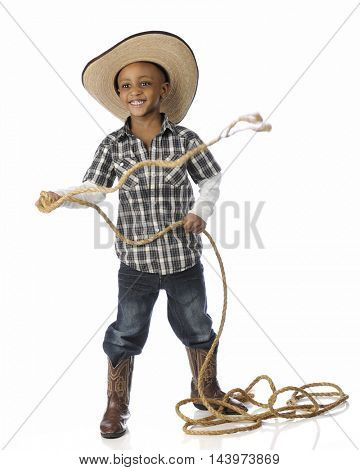 An adorable African American cowboy happily swinging a long rope.  On a white background.