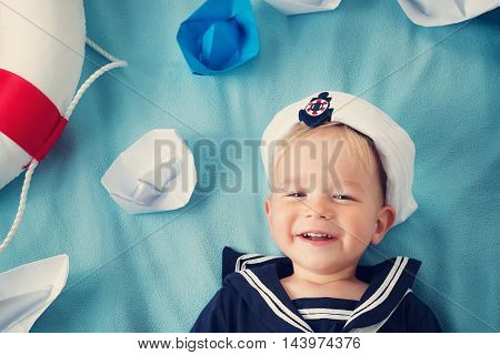 two years old boy playing in sailor hat. Child with paper ships on blue background