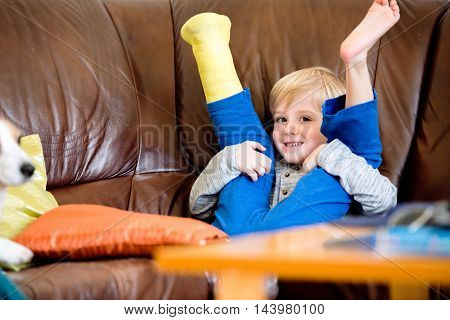 Boy With Broken Leg In Cast Sitting On Couch.