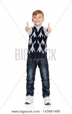 Cute teenager boy standing and showing thumb up sign. Smiling school boy isolated on white background. Full height portrait happy child.