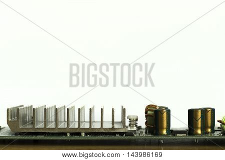 part of computer board heat sink and capacitor on PCB with white background