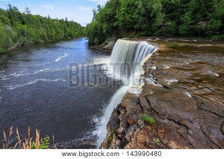 A very picturesque waterfall Tahquamenon Falls and the Tahquamenon River in Summer Michigan's Upper Peninsula USA