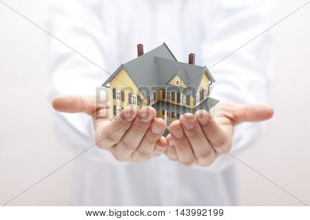 Man holding yellow house miniature