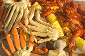 A seafood medley of crab legs crayfish and vegetables poster