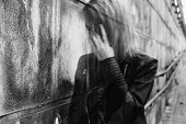 Young woman suffering from a severe disorientation confusion or sadness outdoors in front of a wall. Converted to black and white grain added blurry slightly out of focus. poster