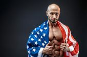 Sexy shredded man with American flag on shoulder looking at camera. Strong bodybuilder with six pack, perfect abs, shoulders, biceps, triceps and chest, personal fitness trainer flexing his muscles. poster