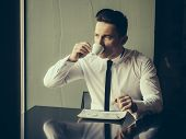 Man young handsome elegant model wears white shirt black skinny necktie sits at table drinks coffee and looks away indoor on grey background poster
