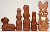 A group of milk chocolate easter bunnies and a chocolate lamb poster