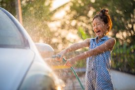 Happy Asian girl washing car on water splashing and sunlight at home