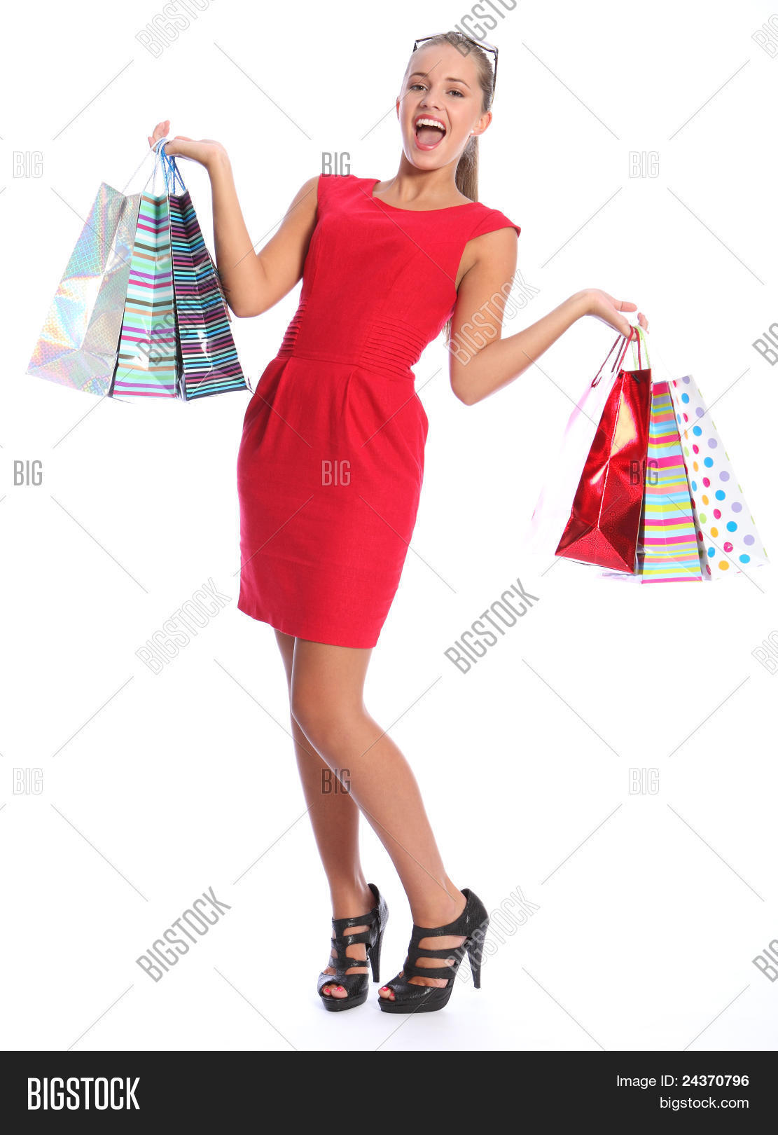 890bff079ab Shopping gift bags held by beautiful sexy young woman with lovely happy  smile wearing black high heeled shoes and short red dress. She has blond brown  hair ...